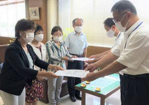 堂山市長公室長(右)と高井教育次長(左)に要望書を手渡す議員団